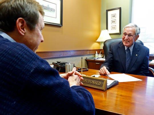 Willie McDonald helps customer Stephen Englert on Dec. 13, 2017, at CedarStone Bank.