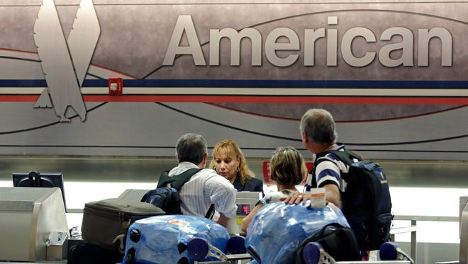 Passengers check in at the American Airlines counter at Miami International Airport on May 27, 2014.