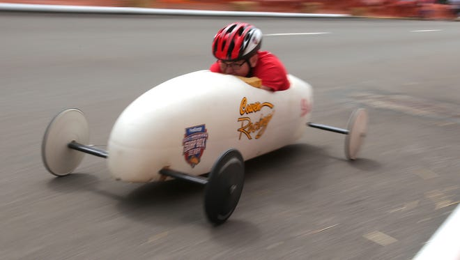 Children ride down North Main Street in the annual Soap Box Derby race on Saturday.