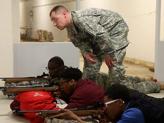 Shawn Legault watches his students during marksmanship training at the Junior ROTC shooting range at the Leadership Academy for Young Men at Charlotte.