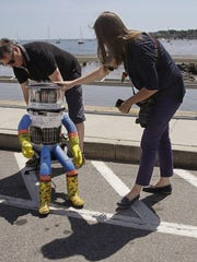 HitchBOT cocreators David Harris Smith, left, and Frauke Zeller get the robot ready for its cross-country journey, which began July 17.
