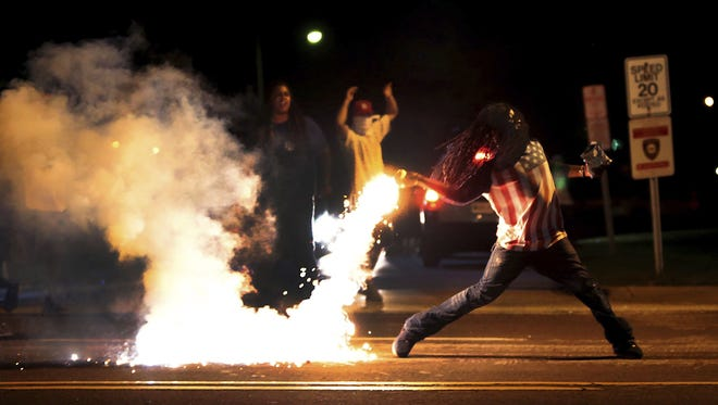 Edward Crawford Jr. throws a container of tear gas back at police officers during a protest against police Aug. 13, 2014, in Ferguson, Mo., four days after a white police officer fatally shot unarmed black teenager Michael Brown. The photo was part of the St. Louis Post-Dispatch's Pulitzer Prize-winning photo coverage of the protests.