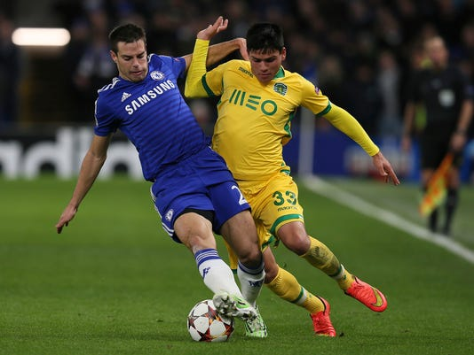 FILE - In this Wednesday, Dec. 10, 2014 filer, Chelsea's Cesar Azpilicueta, left, tussles with Sporting's Jonathan Silva during the Champions League Group G soccer match between Chelsea and Sporting Lisbon at Stamford Bridge in London. On a relatively quiet transfer deadline day in Italy, the bigger news was the players leaving the country. Brazilian defender Emerson Palmieri moved to Chelsea from Roma in a deal worth up to 29 million euros while Japan and Inter Milan defender Yuto Nagatomo joined Galatasaray on loan until the end of the season. Roma immediately replaced Emerson with Argentina left back Jonathan Silva, who joined on loan from Sporting Lisbon until the end of the season with the Giallorossi having the option to make the deal permanent. (AP Photo/Tim Ireland, File)