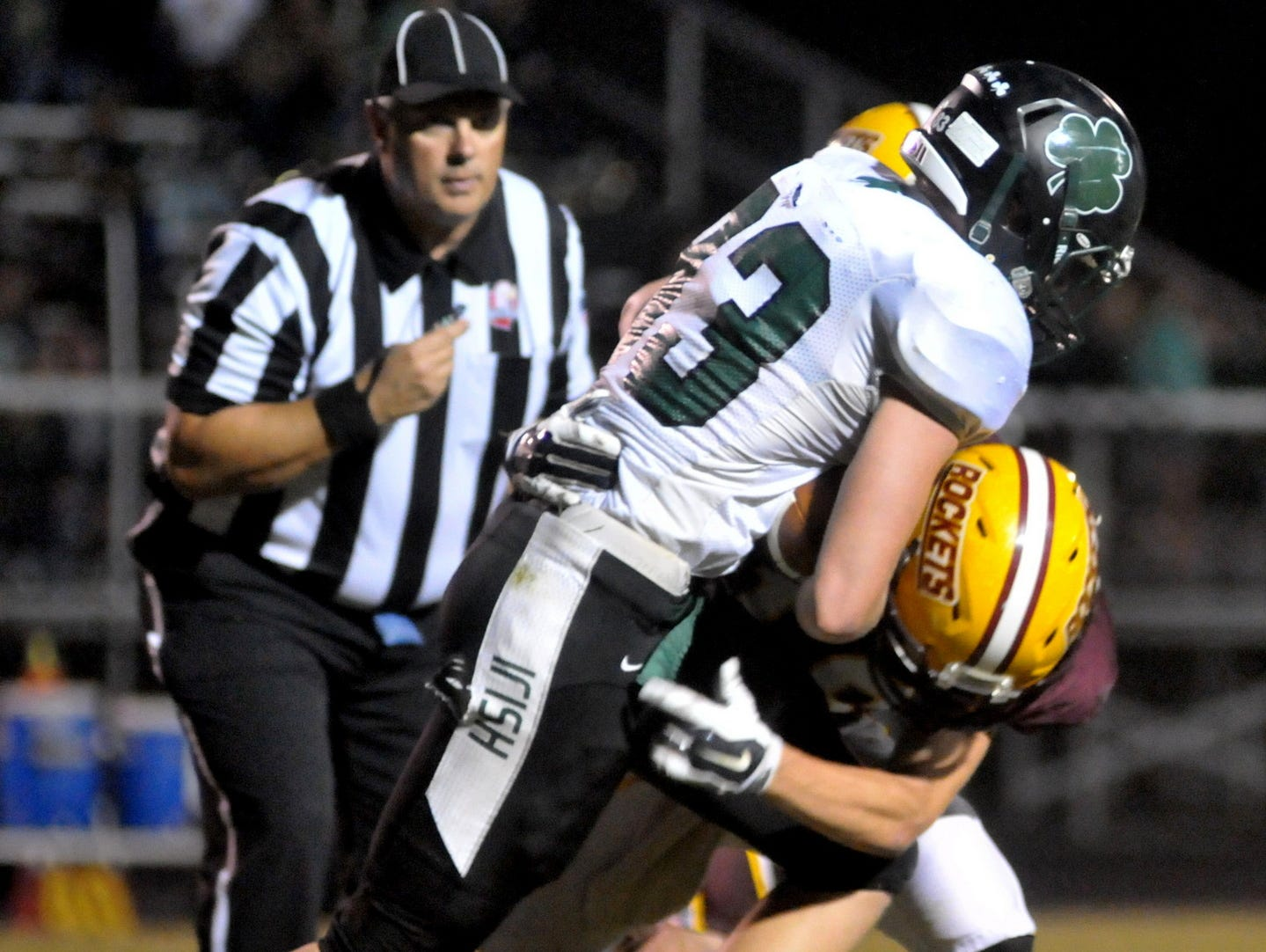 Fisher CatholicÕs Allen McCall runs over a defender Friday night in Sugar Grove. The Irish defeated the Rockets 10-7.