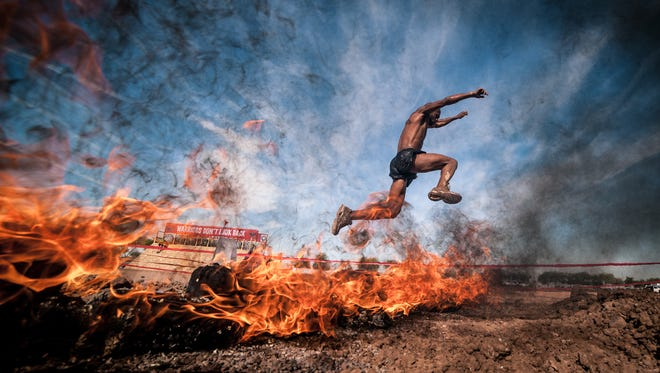 For some, running a 5K isn't enough. They want a barbecue with their exercise. Here a Warrior Dash contestant leaps a pile of flaming logs.
