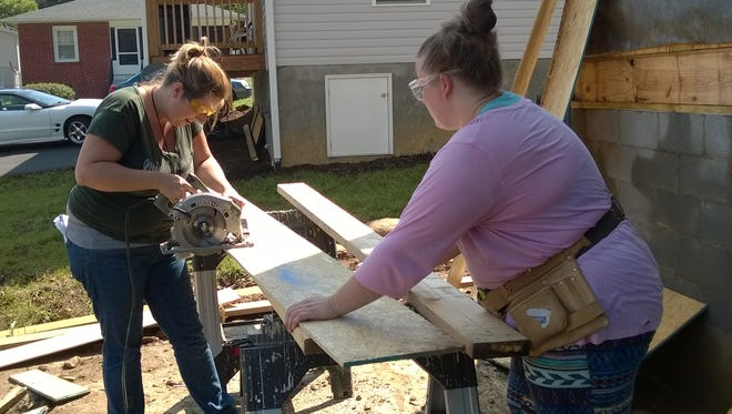 Reporter Beth Walton works with Amanda Ellsworth on her new home in Swannanoa, Ellsworth and her husband, Cory Artrip, are taking part in Mountain Housing Opportunities Self-Help Homeownership program, where participants work together to build their own neighborhood.