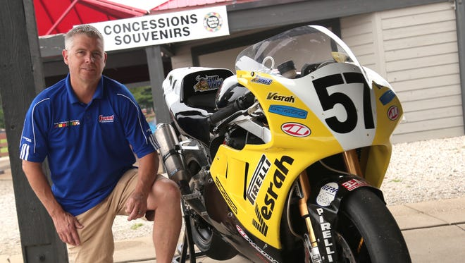 Mid-Ohio Sports Car Course instructor, Mark Junge, kneels next to his 1989 GSX-R750 Suzuki. He will race it in this weekend's Vintage Motorcycle Days.