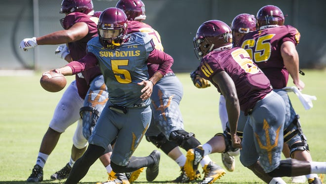 Quarterback Manny Wilkins fakes a hand off to running back Eno Benjamin during a drill on Aug. 15 in Tempe.