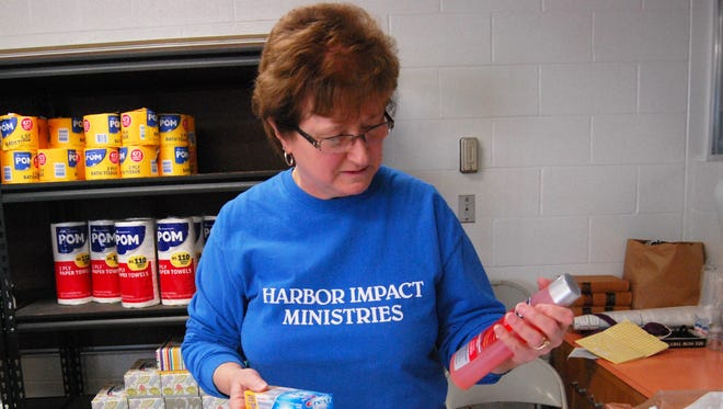 Denise Bishop removes items from bags to stocks shelves in the Bear Necessities pantry at Harbor Impact Ministries in Kimball Township. The group received $1,000 from Visa that was used to replenish the Bear Necessities pantry.
