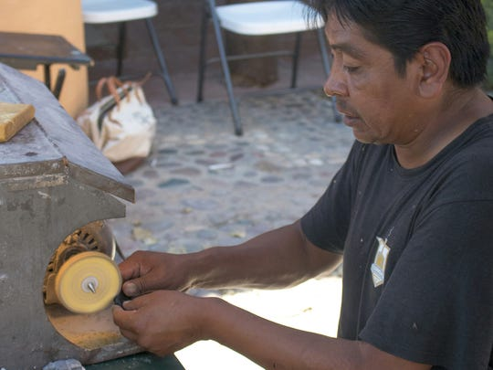 A Zuni fetish carver works on one of his pieces during the 2015 Art Market.