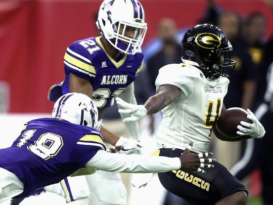 Grambling State's Martez Carter (4) is tackled by Alcorn State's Leishaun Ealey (18) and Jayron Harness (21) during the SWAC championship game on Saturday.
