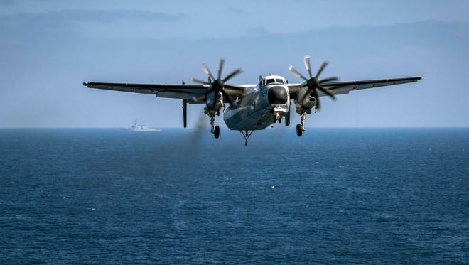 In this image provided by the U.S. Navy, a C-2A Greyhound assigned to the Providers of Fleet Logistics Support Squadron (VRC) 30, prepares to land on the flight deck aboard the aircraft carrier USS Theodore Roosevelt (CVN 71) on Aug. 22, 2017. The search  ended for three sailors missing in the Philippine Sea since a U.S. Navy aircraft crashed on Wednesday, the Navy said.