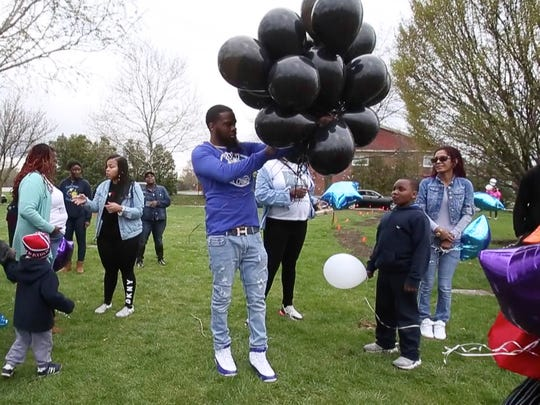 Khalif Friend (center) distributes balloons for release at a memorial for a pair of his murdered cousins at a graveside gathering April 25. Friend was shot and killed in Wilmington Monday.