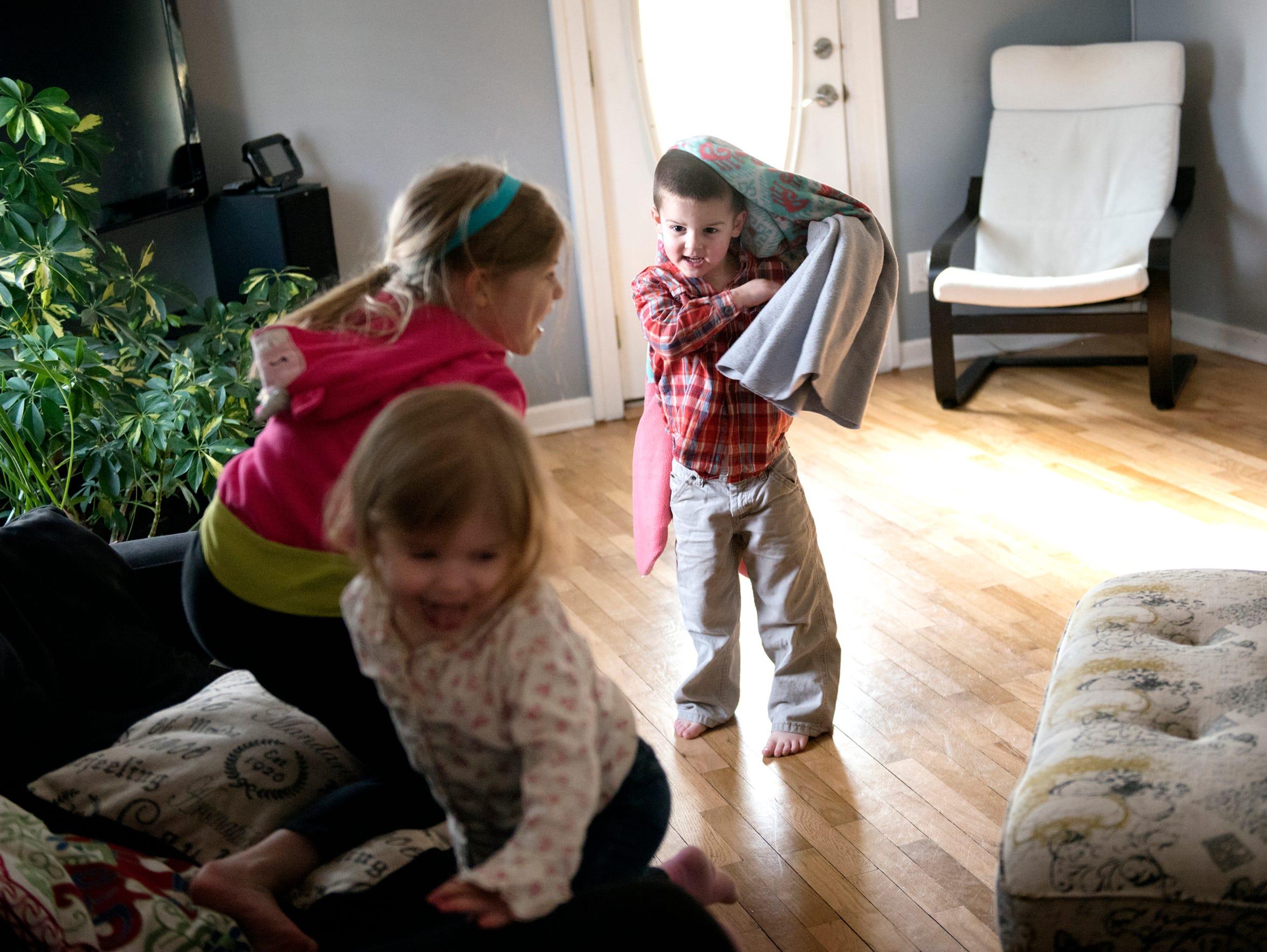 Simeon Neuenschwander, 4, right, pulls a blanket off