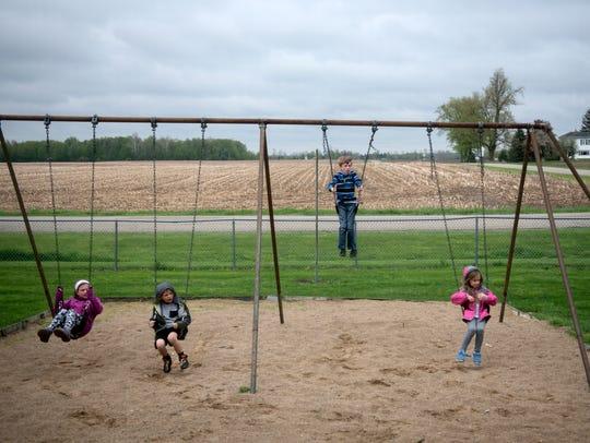 Children swing on the playground equipment at the Strange