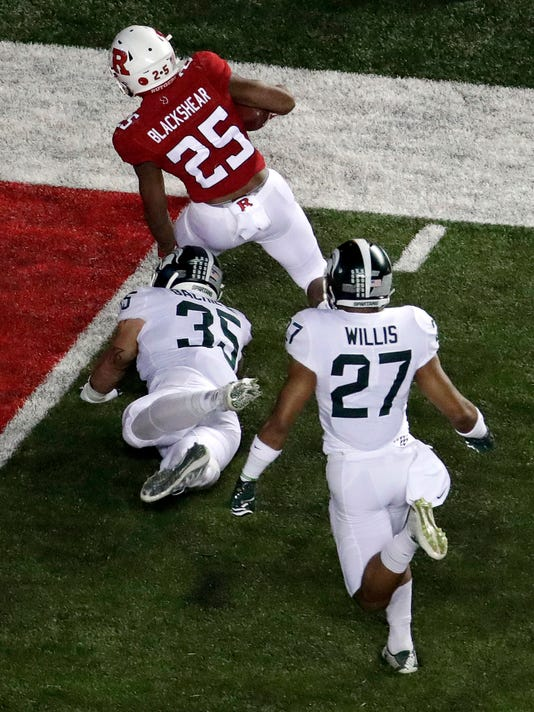 Rutgers running back Raheem Blackshear (25) avoids a tackle by Michigan State linebacker Joe Bachie (35) while scoring on a touchdown pass from quarterback Johnathan Lewis, not pictured, during the first half of an NCAA college football game, Saturday, Nov. 25, 2017, in Piscataway, N.J. (AP Photo/Julio Cortez)