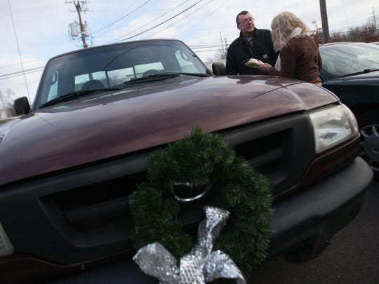 Pete Buchmann and Mary Beth Cichocki stand next to the 2003 Mazda truck that Cichocki gave to Buchmann at Faithful Friends after hearing that he walked 5 miles every day to be with his dog, Buster.