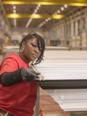 Latasha Jenkins, hired under Milwaukee's Residents Preference Program, assembles a glass panel in 2016 to be used on the Northwestern Mutual tower on the Milwaukee lakefront.