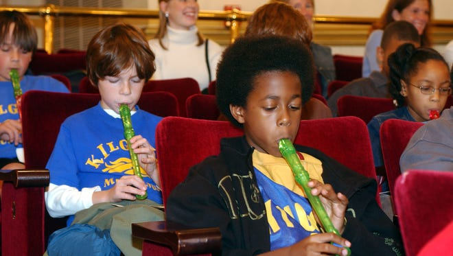 Children play recorders at a concert by the Cincinnati Symphony Orchestra.