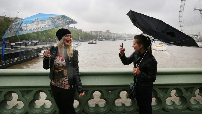 LONDON, ENGLAND - MAY 28:  A girl photographs her friend on Westminster Bridge on May 28, 2013 in London, England. Heavy rain is falling in London and the south east after a warm and sunny bank holiday weekend.  (Photo by Peter Macdiarmid/Getty Images)