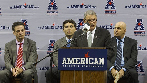 American Athletic Conference commissioner Mike Aresco speaks at the league's NCAA college basketball media day on Wednesday, Oct. 16, 2013 in Memphis, Tenn. At left is louisville coach Rick Pitino. (AP Photo/Lance Murphey)