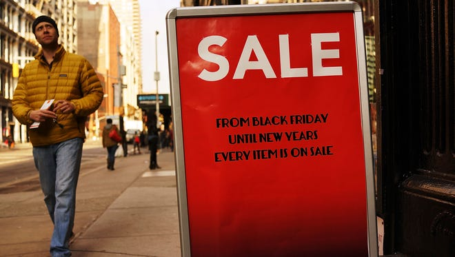 "A ""Sale"" sign stands along Broadway in New York City. The Commerce Department announced retail sales for November on Thursday."