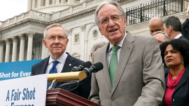 Senate Health, Education, Labor and Pensions Committee Chairman Sen. Tom Harkin, D-Iowa, right, accompanied by Senate Majority Leader Harry Reid of Nevada, urged approval for raising the minimum wage at an April 2, 2014, news conference on Capitol Hill.
