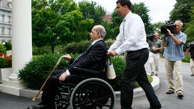 James Brady is pushed by White House deputy press secretary Bill Burton during his visit at the White House on June 16, 2009.