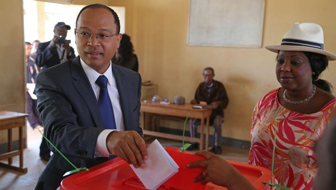 Madagascar presidential hopeful Edgard Razafindravahy casts his ballot as United Nations official Fatma Samoura looks on at a polling station in Antananarivo, Madagascar.