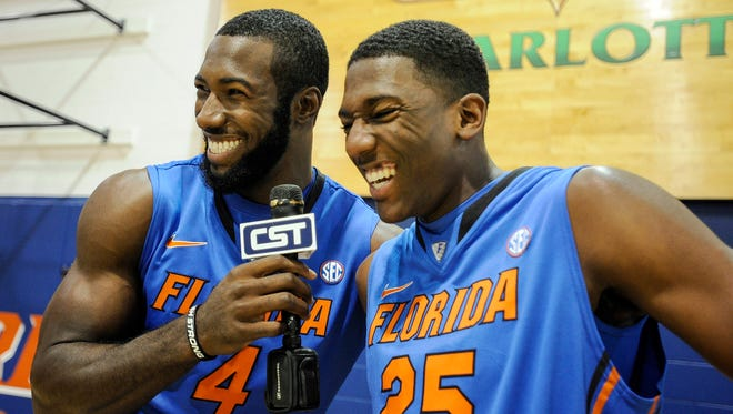 Florida's Patric Young (4) and DeVon Walker (25) kid around with a microphone during the NCAA college basketball team's media day in Gainesville, Fla.