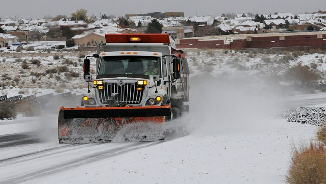 A Deptartment of Transportation plow and sanding truck heads up Paseo del Norte in Albuquerque, N.M., on Nov. 24.
