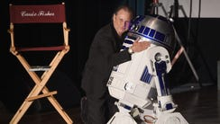 Todd Fisher comforts a mournful R2-D2 at the memorial