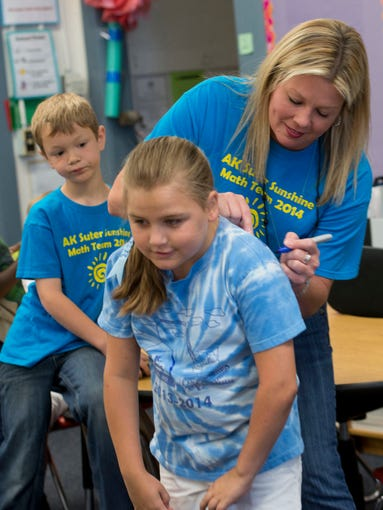 Third-grade teacher Cindy Bradley, center, signs her name on student Madison Brown's, right, shirt, while William Thomas, left, looks on and waits for his turn to sign the shirt on the last day of school at A.K. Suter Elementary Friday morning May 30, 2014.