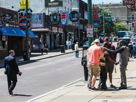 Dylan McCollum, Caleb Cerney, Blake Lariscey and Elijah Hundley, representatives from the Ramp School of Ministry in Hamilton, Alabama, pray for a man on Beale Street on April 24, 2017.