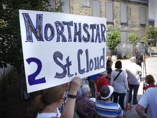 People hold signs during a rally and march in July to support extension of the Northstar commuter rail from Minneapolis to St. Cloud.