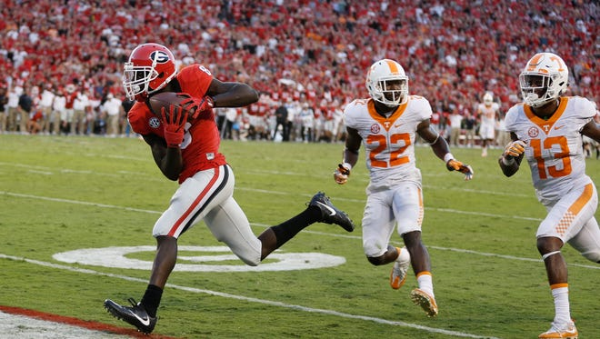 Georgia wide receiver Riley Ridley (8) runs away from Tennessee defensive backs Micah Abernathy (22) and  Malik Foreman (13) to score on a pass from quarterback Jacob Eason with 10 seconds remaining on  Oct. 1, 2016. But  Tennessee scored on the game's last play to win 34-31.