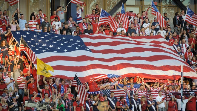 In this 2012 file photo, USA soccer fans cheer as they unfurled a large American flag before a World Cup qualifying match against Guatemala in Kansas City, Kan.