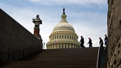 People walk outside of the U.S. Capitol on April 27,
