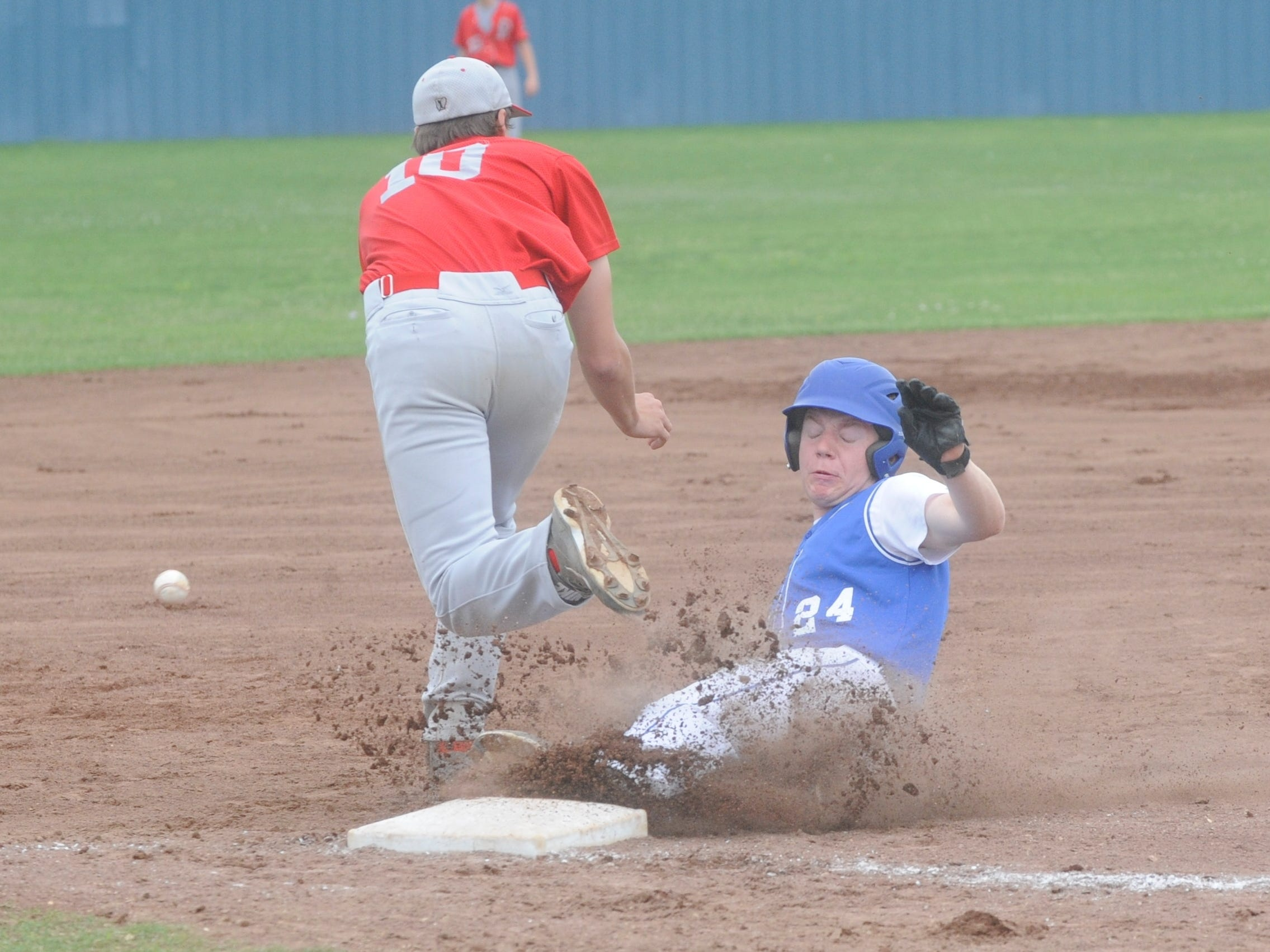 Cotter's Aron Rowe, right, slides safely into third base during the Warriors' 13-5 loss to Rivercrest in the championship game of the 3A Region 3 Tournament on Tuesday at Harrison.