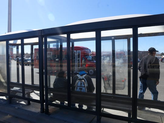 Riders wait to board a Red Apple Transit bus Friday at Orchard Plaza in Farmington.
