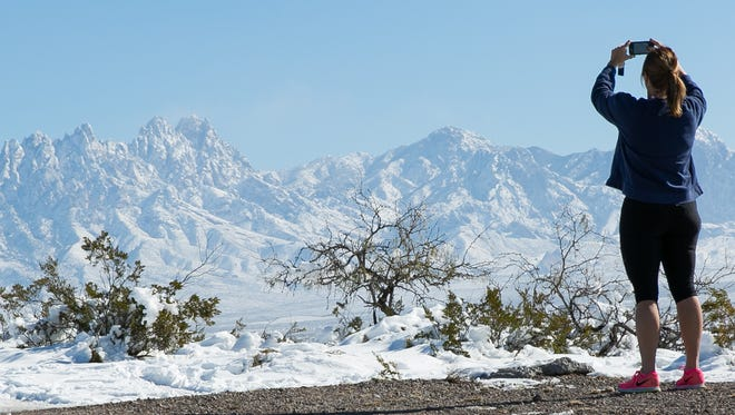 """Kim Aline, who just moved to Las Cruces from San Diego in January, takes a picture of the snow-covered Organ Mountains on Monday just off of Sonoma Ranch Boulevard. """"They should make a scenic-view post here,"""" said Aline. """"It is beautiful."""""""