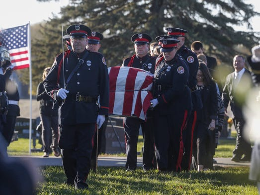 Members of the Urbandale Police Department carry officer