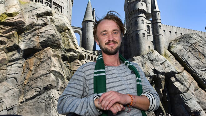 Tom Felton poses in front of Hogwarts Castle as he gives USA TODAY a tour of The Wizarding World of Harry Potter at Universal Studios Hollywood.
