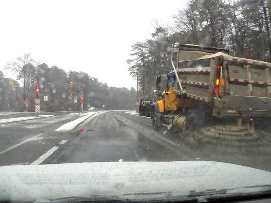 An Ocean County truck speads salt along Burnt Tavern Road in Brick Township hursday morning.