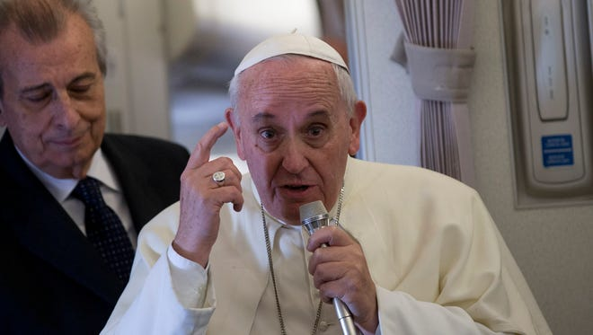 Pope Francis, right, gestures as he talks with journalists during his flight from Manila to Rome on Monday.