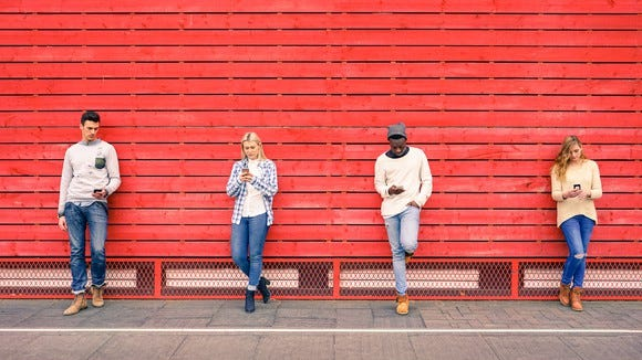 Four young people standing in front of a red wall using their cell phones