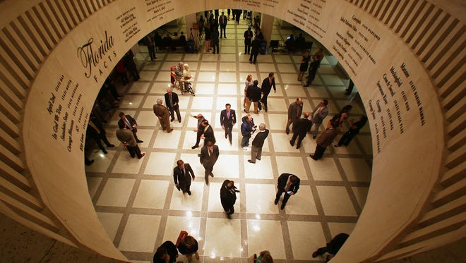 Lobbyists, lawmakers, journalists, and guests fill the fourth floor Rotunda of the Florida Capitol, Friday, May 2, 2104.
