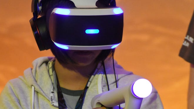 Qiwen Cui tries out the 'Farpoint' VR game during the opening day of the Electronic Entertainment Expo at the Los Angeles Convention Center.
