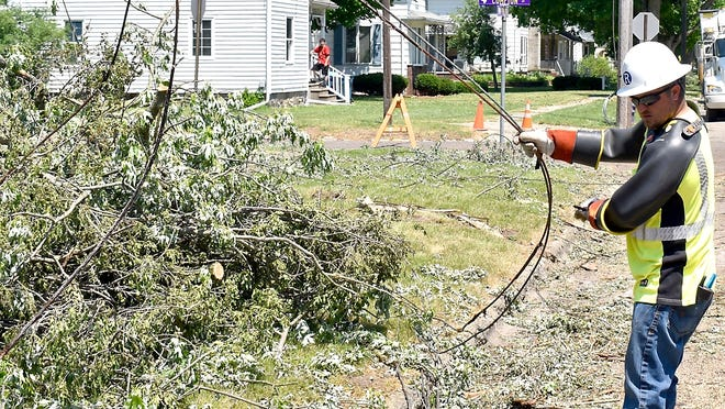 Linemen from Ruhorn Electric untangle downed power lines Friday on Walker Street in Bronson.