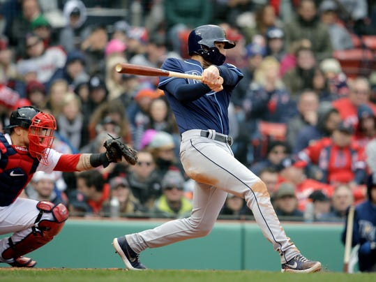 Tampa Bay Rays' Brad Miller, right, hits an RBI single as Boston Red Sox's Christian Vazquez, left, looks on in the fifth inning of a baseball game, Sunday, April 8, 2018, in Boston. (AP Photo/Steven Senne)